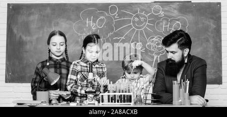 Wissenschaft beinhaltet Theorie. Schule Chemie Experiment. Erklären der Chemie zu Kindern. Faszinierende Chemie Lektion. Man bärtige Lehrer und Schüler mit Reagenzgläsern im Klassenzimmer. Schule Chemie Labor. - Stockfoto