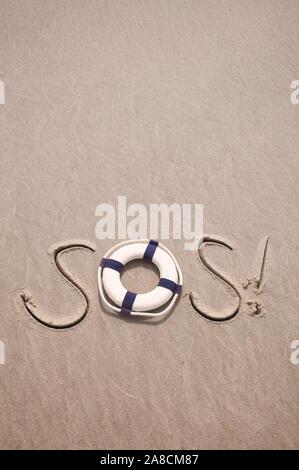 SOS-Nachricht handschriftlich am Strand mit Lebensretter in glattem Sandkopierraum - Stockfoto
