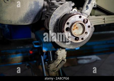 Eine Nahaufnahme der hinteren Bremsanlage eines Autos mit Nabe auf eine Hebebühne in einem Fahrzeug Werkstatt. Auto Service Industrie. - Stockfoto