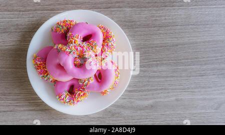 Rosa glasierten Mini Donuts in Weiß Platte auf dem Holztisch. Süße Speisen Hintergrund - Stockfoto