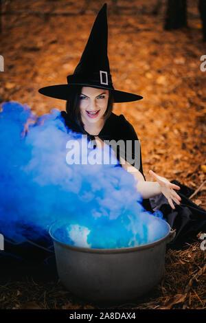 Schwarze Hexe sitzt vor dem Kessel, aus dem blauen Rauch fällt. - Stockfoto