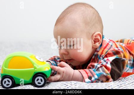 Baby Junge spielt mit einem grünen wenig Auto - Stockfoto