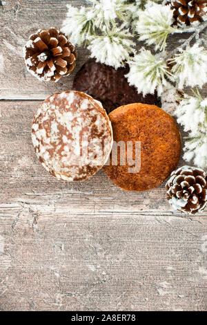 Nürnberger Lebkuchen, Lebkuchen mit Tannenzapfen und Schnee zeder Fir Tree Zweig auf rustikalen braunes Holz panel Hintergrund mit Kopie Raum abgedeckt. Zu - Stockfoto