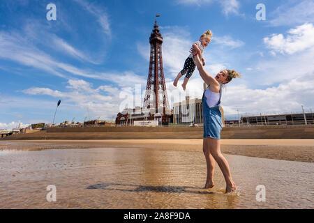 Eine hübsche junge Mutter hält Ihr süsses toddle Tochter in die Luft am Strand von Blackpool mit dem berühmten Blackpool Tower im Hintergrund, Tourismus Foto