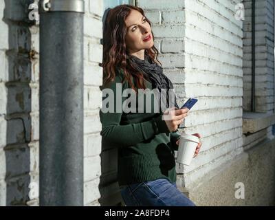 Junge Frau mit roten Haaren können Sie über Ihr Handy und trinken Kaffee aus einer Tasse zum Mitnehmen. - Stockfoto