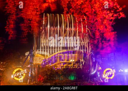 Helsinki, Finnland - 19. Oktober 2019: Der Karneval von Licht am Linnanmaki Vergnügungspark. Fahrten, Kieputin Ketjukaruselli und Vuoristorata in Bewegung - Stockfoto
