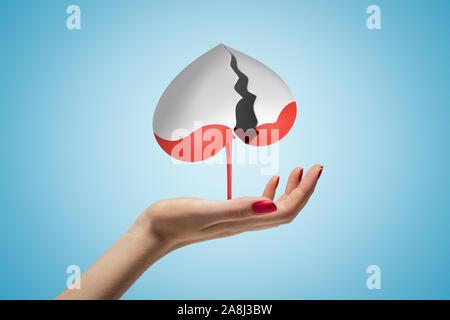 Seitenansicht der Frau Hand nach oben und schwebenden Grau gebrochene Herzen auf den Kopf, mit roter Flüssigkeit abtropfen, auf hellblauem Hintergrund. - Stockfoto