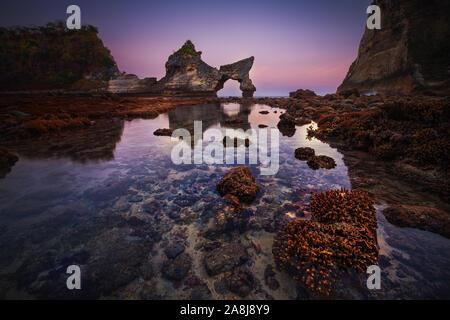 Atuh Strand nach Sonnenuntergang. Coral Reef bei Ebbe. Schöne arch und Pinnacle. Nusa Penida, Indonesien. Blaue Stunde. - Stockfoto