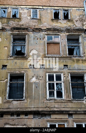 Alten verlassenen Wohnung Haus mit beschädigter Fassade und sich selbst zusammenzuzucken Windows