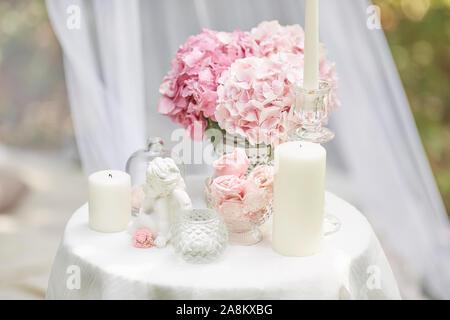 Grußkarte im Shabby Chic Stil. Rosa hortensie Blumen, statuette eines Engels, Marshmallows, Kerzen auf dem Tisch. - Stockfoto