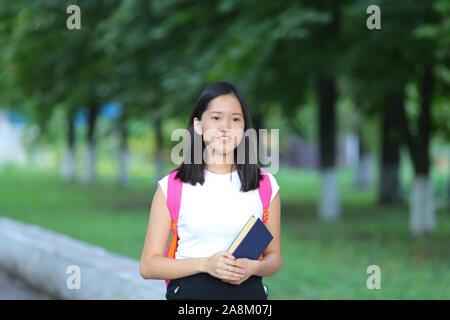 Mädchen weibliche Teenager mit schwarzen Haaren in einem Bob weiße ostasiatischen Frau grünen Park mit einem Rucksack-Hintergrund. Lady hält, Zifferblätter, schieben Sie Ihren Finger, smili - Stockfoto