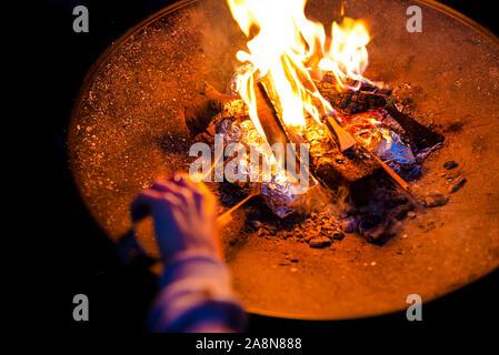Kartoffeln eingewickelt in Alufolie gebacken in einem Lagerfeuer. - Stockfoto