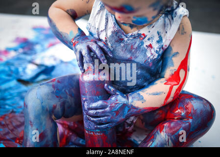 Eine entzückende kleine Kleinkind, Mädchen hat Spaß beim Spielen mit Farben malt, unordentlich und haben viel Spaß, in einer familiären Umgebung Schuß - Stockfoto
