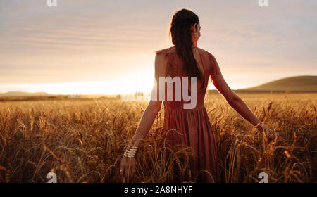 Junge Frau hand Gefühl oben ein Feld von Weizen in goldenes Sonnenlicht bei Sonnenuntergang. - Stockfoto