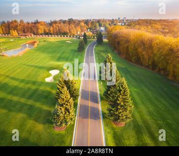 Straße durch den Golfplatz bei Sonnenuntergang im Herbst. Luftaufnahme - Stockfoto
