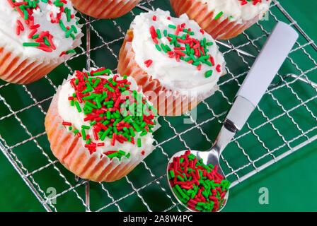 Hausgemachte red velvet Weihnachten Cupcakes mit Frischkäse weiße Tüpfelchen garniert mit Urlaub in den Farben rot grün und Weiß besprüht. - Stockfoto