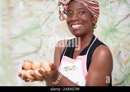 Junge Frau in einem Studio mit grünem Hintergrund, holding Bio-Eier in den Händen - Stockfoto