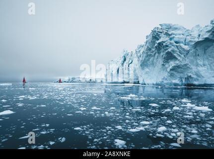 Schöne rote Segelboot in der nächsten zu einem massiven Eisbergs zeigt die Skala Arktis. Kreuzfahrt unter schwimmende Eisberge in der Diskobucht Gletscher midnigh