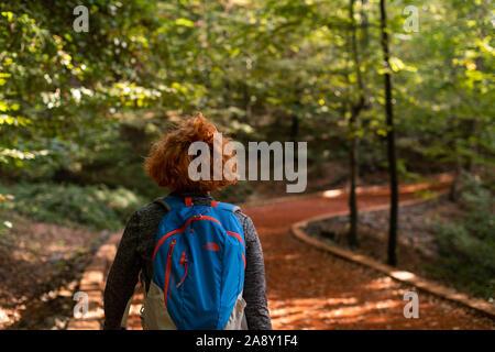 Junge Frau zu Fuß in den Wald. Abenteuer Stil. Farben des Herbstes. Die herrliche Natur und die jungen Mädchen. Konzept für den Außenbereich und Parks. - Stockfoto