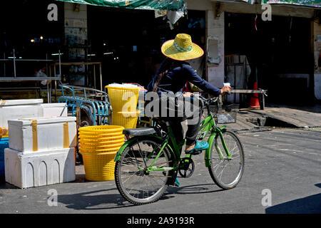 Frau, die Fahrrad fährt. Traditionelle thailändische Straßenszene - Stockfoto