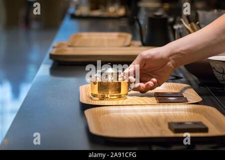 Barista männliche Hände eine Teekanne aus Glas mit Tee in Strängen auf einem Tablett auf einen Coffe Shop counter in Busan, Südkorea - Stockfoto