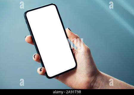 Mockup Bild der Frau hand mit dünnen Rahmen Handy mit leerer Bildschirm in glänzendem Unternehmensumgebung - Bild - Stockfoto