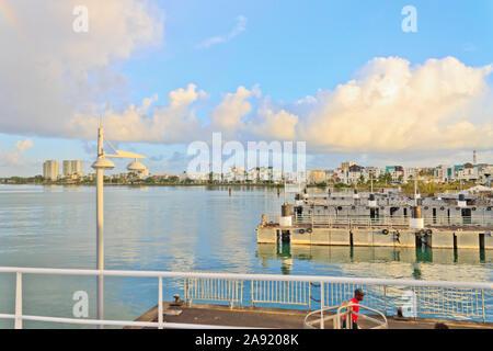 Einheitliche Arbeitnehmer - ein stevedore, ziehen einen Wagen in den frühen Morgenstunden an der Seehafen in Guadeloupe bei Sonnenaufgang mit einem blau leuchtenden bewölkter Himmel hinter ihm - Stockfoto