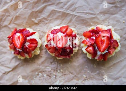 Sehr lecker Muffins mit frischen Erdbeeren liegen auf Kraftpapier. - Stockfoto