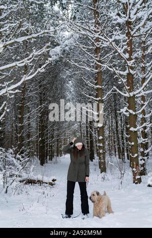 Frau mit Hund im Winter Wald - Stockfoto