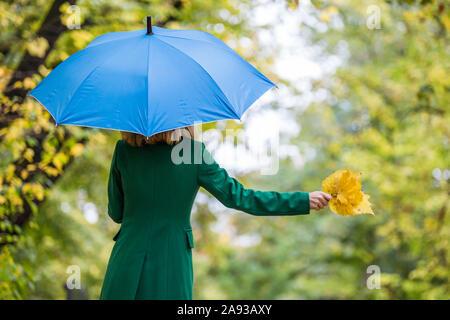 Frau mit Sonnenschirm und fallen Blätter beim Stehen in den Park. - Stockfoto