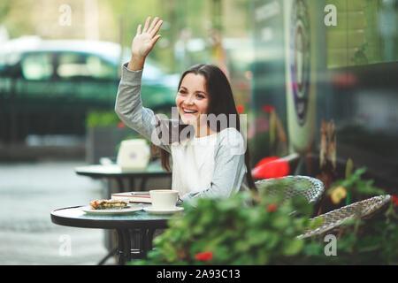 Junge Modell suchen Frau mit langen braunen Haaren sitzt in einem Café in den Brunch. Kaukasische Frauen mit natürlichen Make-up auf den Lippen nach oben schaut, während sie am Tisch sitzen. Mädchen winken - Stockfoto