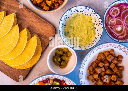 Vegan hausgemachte leckere Tacos mit Süßkartoffeln, Tofu, Avocado Sauce, Jalapeno und Mango Salsa - Stockfoto
