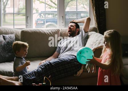 Eine müde Vater liegt auf der Couch, während seine Kinder um ihn herum spielen. Stockfoto