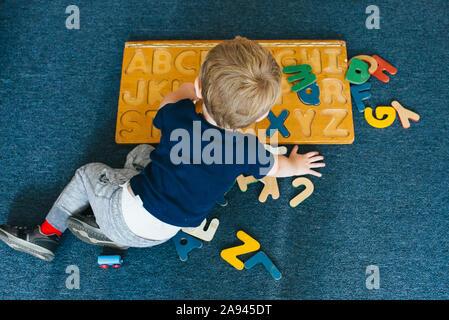 Ein kleiner Junge spielt mit einem Alphabet Puzzle. - Stockfoto