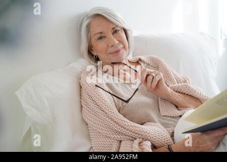 Schöne ältere Frau im Bett lesen - Stockfoto