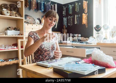 Frau arbeitet an einem Edelstein Halskette als Hobby - Stockfoto