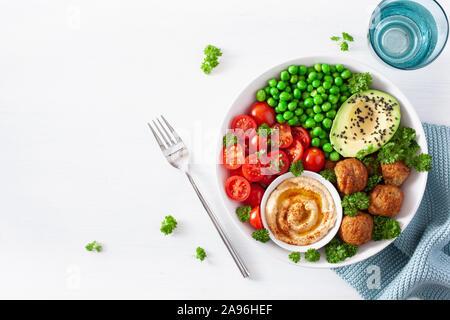 Gesund vegan Mittagessen Schüssel mit falafel hummus Tomate avocado Erbsen - Stockfoto