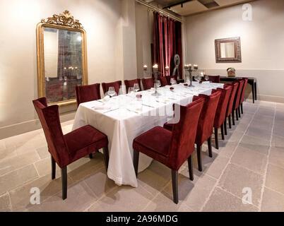 Lange formellen Esstisch in einem eleganten Restaurant mit einem weißen Tuch, Besteck und Gläser mit brennenden Kerzen in der kandelaber eingestellt - Stockfoto