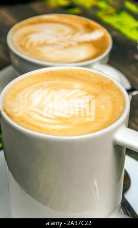 Zwei Kaffee mit Herz auf einem Teller serviert. - Stockfoto