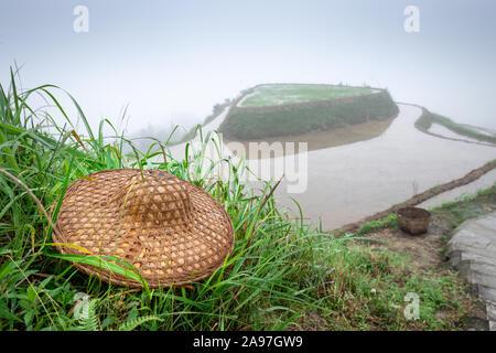 Guilin, China Reisterrassen und Arbeitnehmer hut mit dichtem Nebel. - Stockfoto