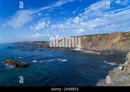 Aljezur, Portugal - 26. August 2019: ein Fischer fischen in einem Felsen in der Nähe des Esteveira Strand (Praia da Esteveira), in Aljezur, Algarve. - Stockfoto