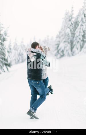 Ein Paar aus Gewirken Kleider Spaziergänge im Winter im Wald mit Bäumen - Stockfoto