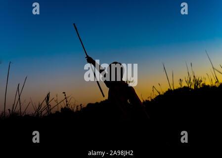 Silhouette der Junge spielt in der Dämmerung im Sommer mit einigen Sticks als Waffen. - Stockfoto