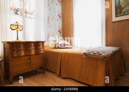 Einzelbett mit gefalteten Decke Decke, antike hölzerne Kommode mit Tiffany Lampe im Schlafzimmer mit Birkenholz Dielen in einem alten 1920er Haus - Stockfoto