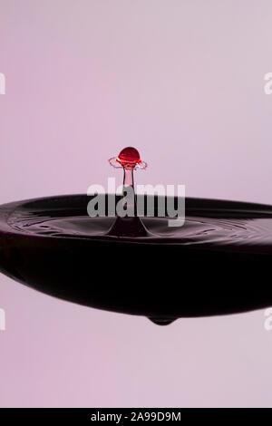 Farbiges Wasser Tropfen an die genaue Zeit freigegeben zu kollidieren und bilden eine Form - ein Regenschirm in einer Suppe Löffel - Stockfoto