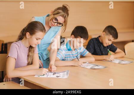 Lehrer helfen der Schule schreiben Test im Klassenzimmer. Bildung, Schule, lernen, Personen Konzept