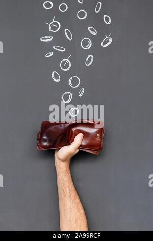 Verdienen Sie Geld mit einem braunen Lederetui in einer Hand vor einer Tafel mit Hand gezeichnet Münzen statt - Stockfoto