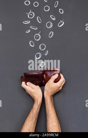 Verdienen Sie Geld mit einem braunen Lederetui in zwei Händen vor einer Tafel mit Hand gezeichnet Münzen statt - Stockfoto