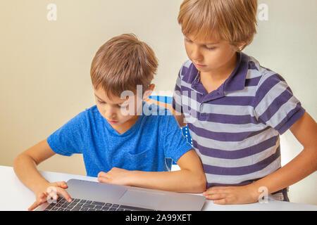 Fokussierte kind Eingabe laptop computer und andere Kind ihm helfen. Schule, Lernen, e-Learning - Konzept - Stockfoto