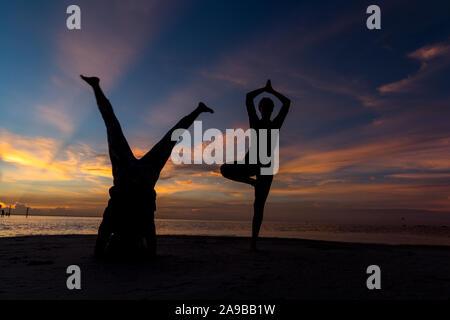 Yoga am Strand. Yoga Praxis unter Freunden am Strand am Meer. Übung Flexibilität und meditieren - Stockfoto